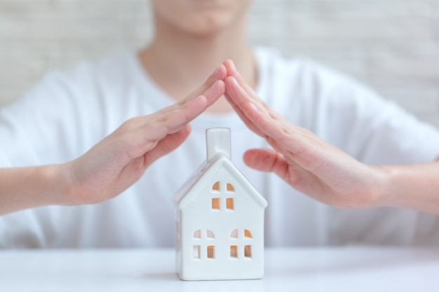 Children's hands over house. home security and protection concept. stay at home concept.