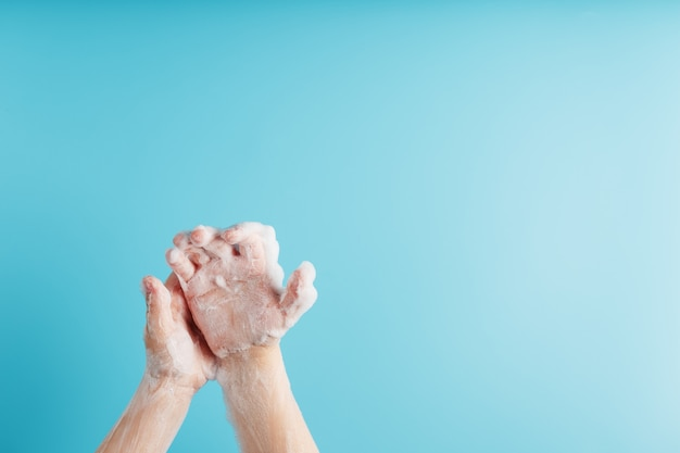 青、上面の石鹸の泡で子供の手。