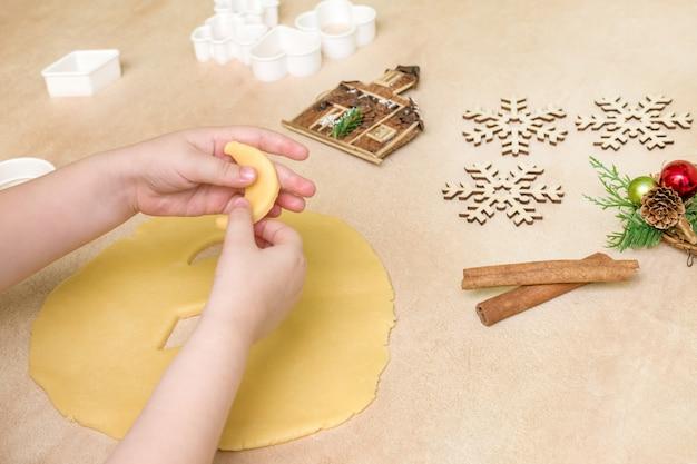 子供の手がクリスマスクッキーを作る