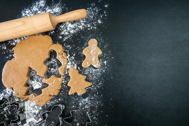 子供の手は、木製のテーブルの上に新年のジンジャーブレッドクッキーを作ります。クッキーカッターでクッキーを作る。新年とクリスマスのコンセプト。