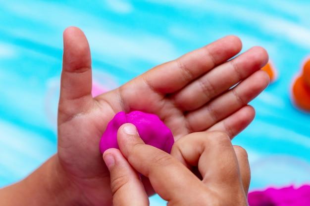Children's hands mold colorful dough close-up. childhood infancy kids babies education concept