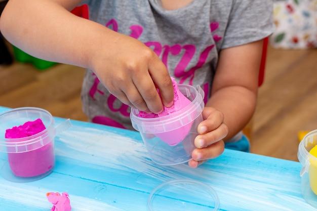 子供の手はカラフルな生地のクローズアップを形成します。幼年期の幼児の赤ちゃん教育コンセプト