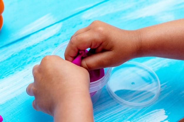 Children's hands mold colorful dough close-up. childhood kids education concept