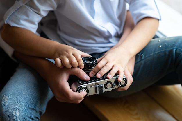 Детские руки мальчика и девочки держат старый пленочный фотоаппарат. день семьи