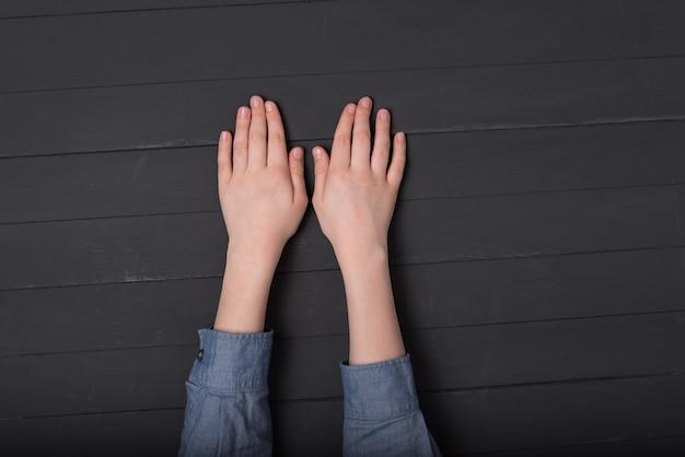 Детские руки на черном фоне. вид сверху рук в рубашке.