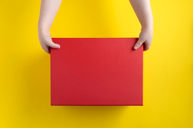 赤い段ボール箱を開く子供の手。