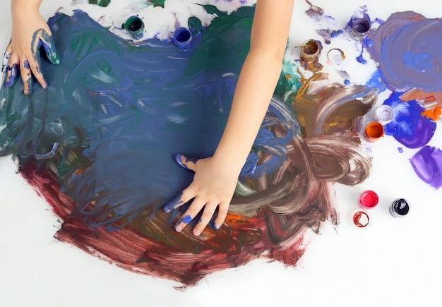 Детские руки рисуют картину красками на белой поверхности