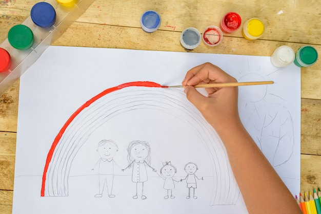 Children's hands paint a drawing with a brush and paints. top view