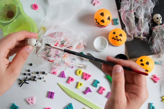 子供の手は、ペンキで包帯にペンキを塗ります。木製のテーブルに絵の具で紙、包帯、粘土。ハロウィーンのポストカードスパイダーとクモの巣、幽霊のようなスケルトン。子供のための工芸品