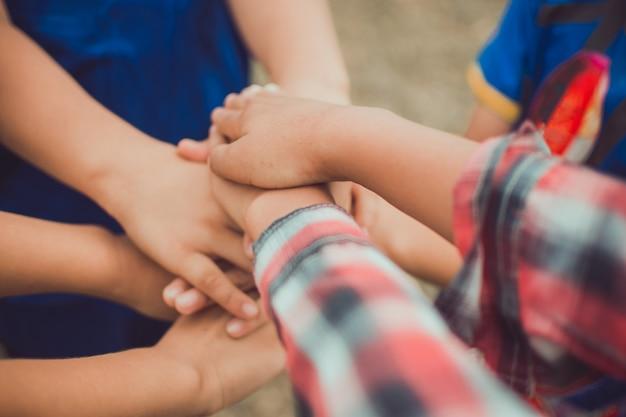 子供の手が上に積まれています。子供たちのチームと小さな男たちの間の建物。チームで遊ぶ。