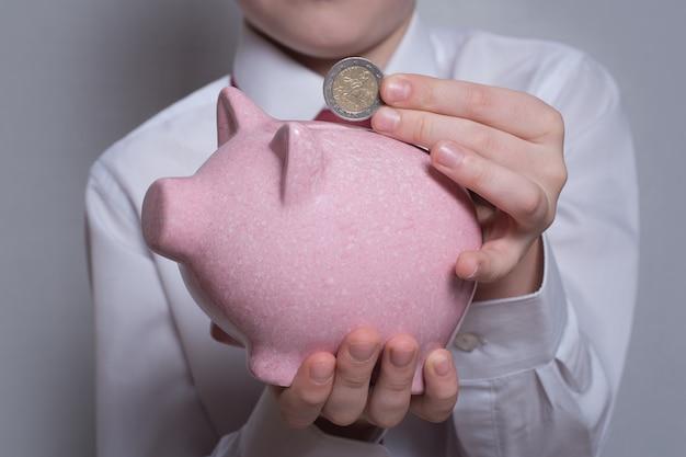 Children's hands put a coin in a pink piggy bank.