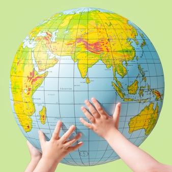 아이들의 손이 지구 모양의 공을 들어 올립니다.
