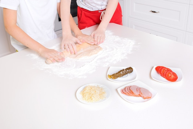 Children's hands roll out the pizza dough on a white table. having fun together in the kitchen. view from above.