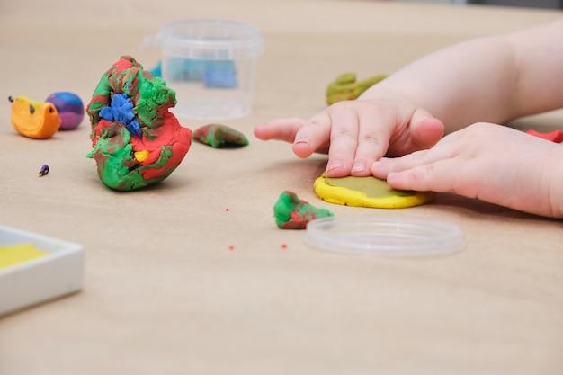 Детские руки лепят круг из желтого пластилина, девочка играет пластилином за столом Premium Фотографии
