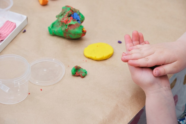 Children's hands sculpt a circle from yellow plasticine, a girl plays with plasticine at the table