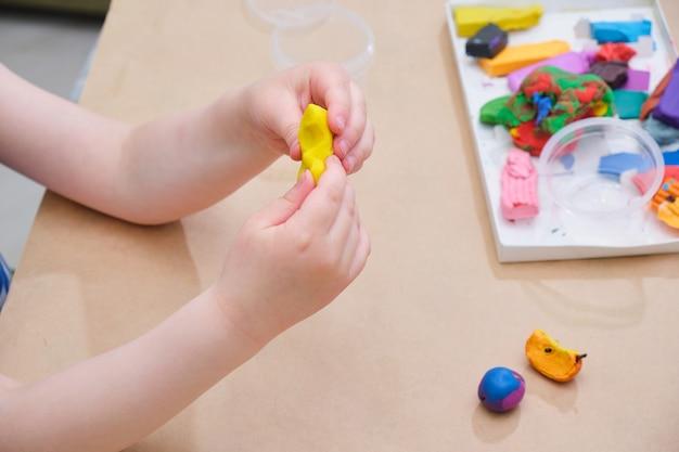 Детские руки лепят из пластилина за столом, девочка играет с пластилиновой копией пространства