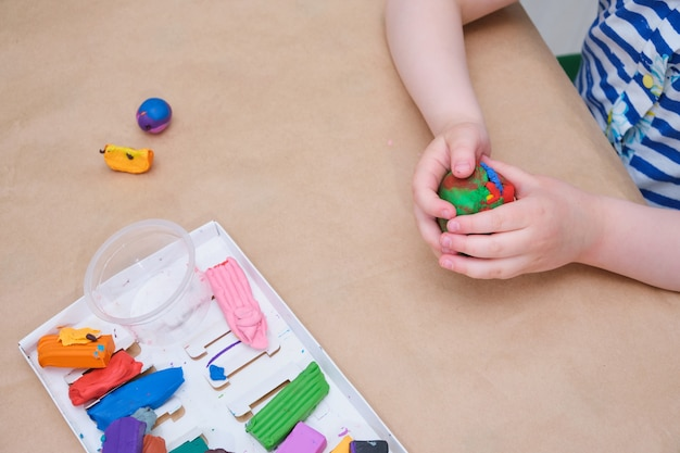 Children's hands sculpt from plasticine at the table, a girl plays with plasticine copy space
