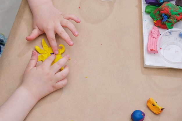 Children's hands sculpt the sun from plasticine at the table, a girl plays with plasticine