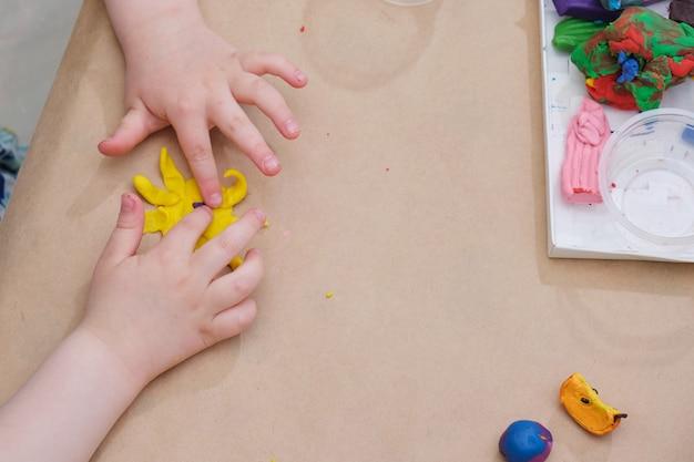 Детские руки лепят солнышко из пластилина за столом, девочка играет с пластилином Premium Фотографии