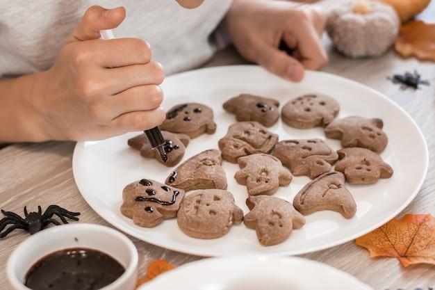 Детские руки выдавливают из шприца шоколадную глазурь на имбирное печенье на хэллоуин на тарелке. приготовление угощений для празднования хэллоуина. образ жизни