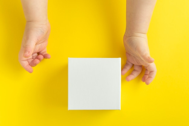 Children's hands and white cardboard box on yellow background, top view. copy space. mock up.
