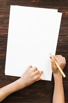 Детские руки с маркером и листом бумаги