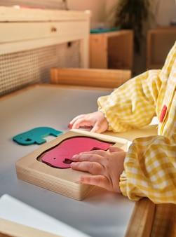 보육원에서 몬테소리 학습 퍼즐이있는 어린이 손
