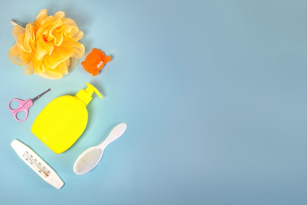 Children's hygiene: bath items, shampoo bottle, rubber toy, sponge, comb, thermometer, safety scissors top view, on a blue background. copy space. children's personal care kit. bath accessories.