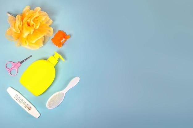 Детская гигиена: банные принадлежности, бутылка шампуня, резиновая игрушка, губка, расческа, термометр, ножницы безопасности вид сверху, на синем фоне. копировать пространство. детский комплект личной гигиены. банные принадлежности.