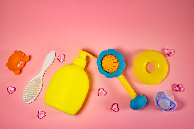 Детская гигиена: банные принадлежности, бутылка шампуня, резиновая игрушка, губка, расческа, термометр, ножницы безопасности вид сверху, на розовом фоне. детский комплект личной гигиены. банные принадлежности.