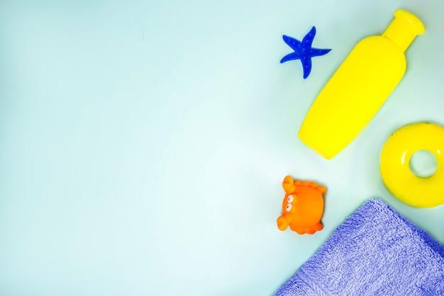 Детские принадлежности для купания: шампунь, полотенце, игрушки морская звезда, спасательный круг, краб, на синем фоне. банные принадлежности плоская. уход за младенцем. скопируйте пространство.