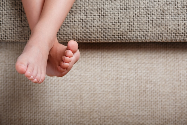 Children's legs close-up hanging from the sofa in the room. baby toes while baby is sitting on the armchair