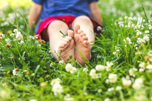 Детские ножки мальчика, сидящего на зеленой солнечной траве, выборочный фокус, мягкий фокус