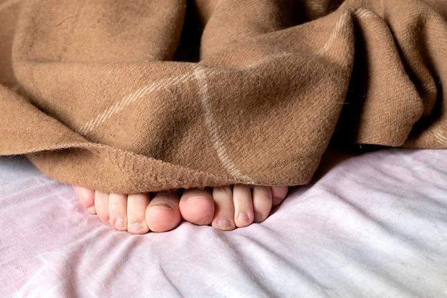 Детские ножки торчат из-под теплого пледа