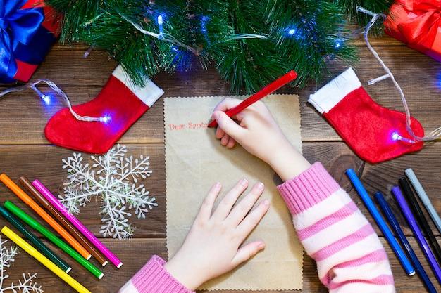 サンタクロースへの子供の手紙。小さな女の子は木製のテーブルにマルチカラーフェルトペンで手紙を書く