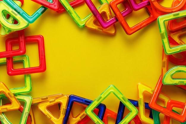 Детский магнитный конструктор или конструктор. детали, геометрические фигуры на желтом фоне. плоская планировка, копирование пространства.