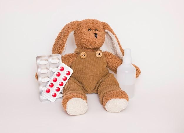 어린이 약. 옆에 약과 정제가 있는 부드러운 어린이 장난감 개. 어린이의 건강과 질병, 바이러스로부터 어린이 보호의 개념.