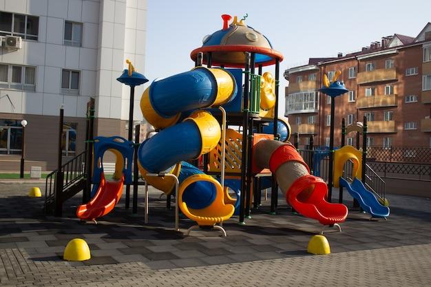 Детская разноцветная пластиковая площадка во дворе многоэтажного дома.