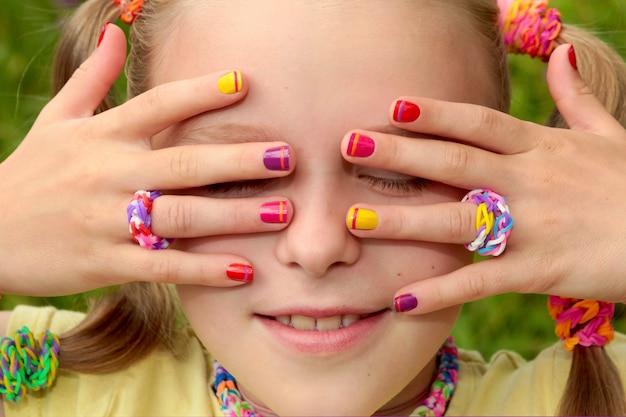 여름 날에 고무 밴드가있는 가벼운 소녀에 줄무늬가있는 어린이 여러 가지 빛깔의 매니큐어.