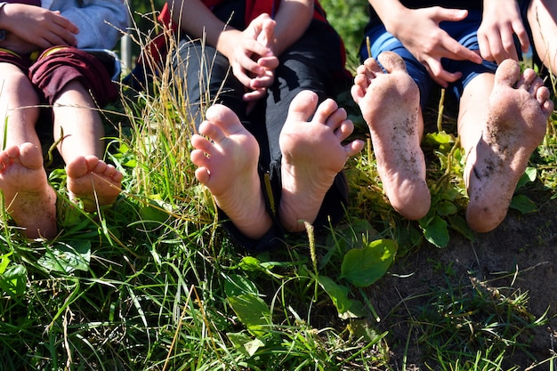 Children's naked feet of legs outdoors. children sit on a grass and show legs.