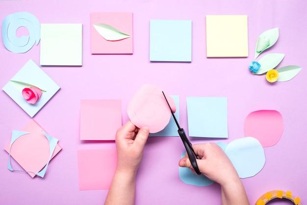 Детские ручки вырезают кружочки из разноцветных наклеек.