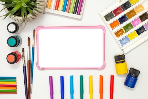 Детский розовый цифровой планшет с пустым экраном на белом столе с разноцветными принадлежностями для рисования