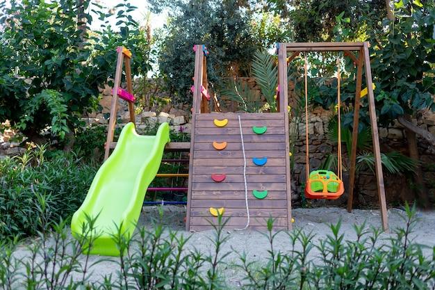 어린이 놀이터는 그네, 미끄럼틀, 암벽 등반이 있는 푸른 나무와 모래 사이에 있는 나무와 생태적 공간입니다.