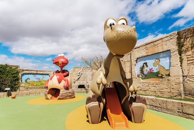 Children's playground with slides in the shape of cute dinosaurs.