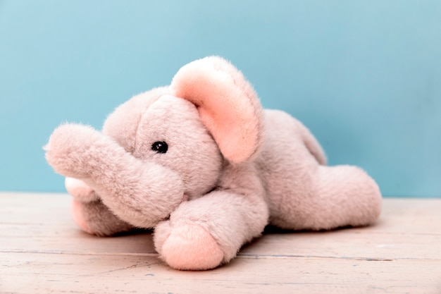 Children's plush elephant on a white wooden table with blue