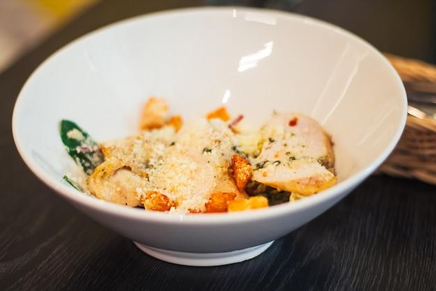 Детская порция салата цезарь, в белой глубокой тарелке