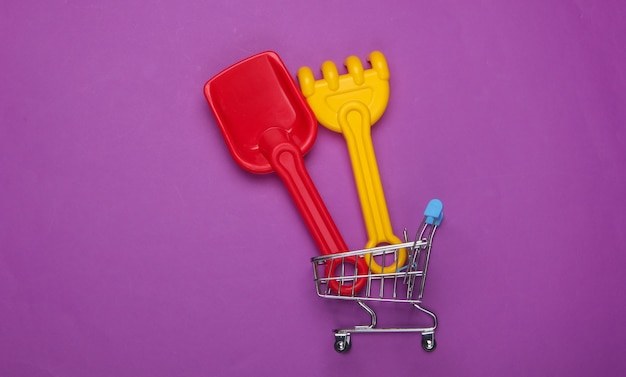 紫色のショッピングカートのサンドボックスまたはビーチ用の子供の熊手とシャベル