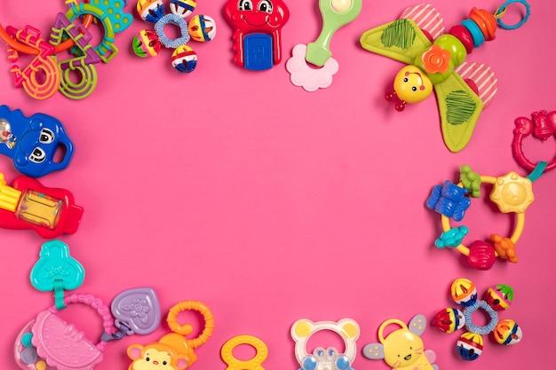 분홍색 배경에 플라스틱에서 아이들의 딸랑이. 평면도. 공간을 복사합니다. 플랫 레이