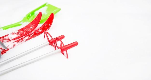 スティックと緑の雪かきが付いている子供の赤いスキー-雪の中でのレイアウト