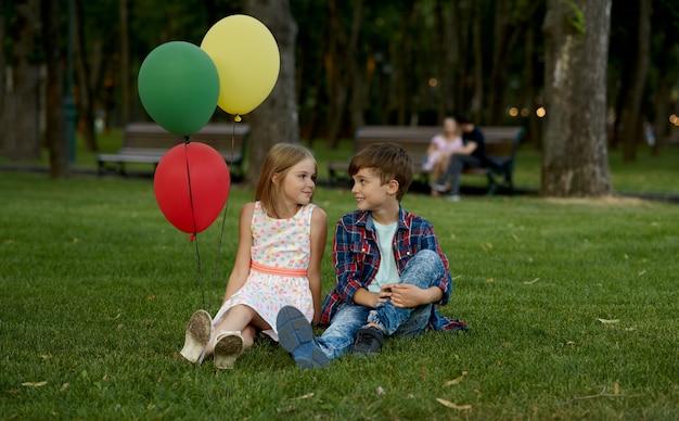 サマーパークでの子供のロマンチックなデート、友情、初恋。草の上に背中合わせに座っている気球を持つ少年と少女。屋外で楽しんでいる子供たち、幸せな子供時代